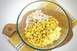 Выложить в миску ананас, кукурузу и куриное филе